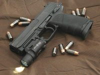 HK_USP_45_surrounded_by_.45_caliber_Hornady_TAP_%28%2BP%29_jacketed_hollow_point_rounds.jpg
